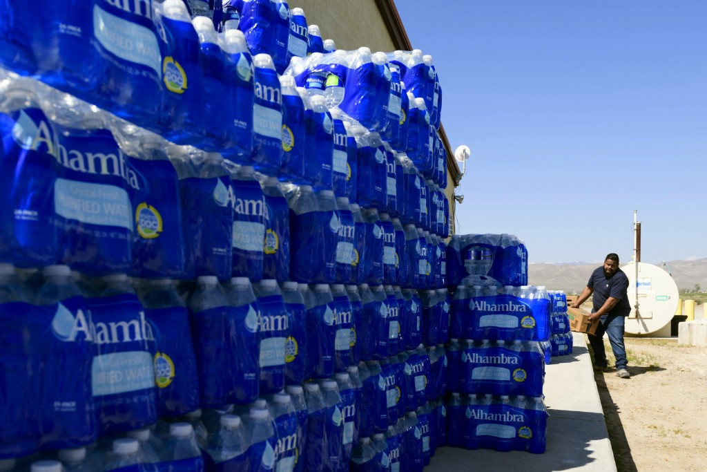 Tommy Gutierrez, a Paiute tribe member, helps load up some of the thousands of plastic water bottles that are distributed weekly to the Yerington Paiu...