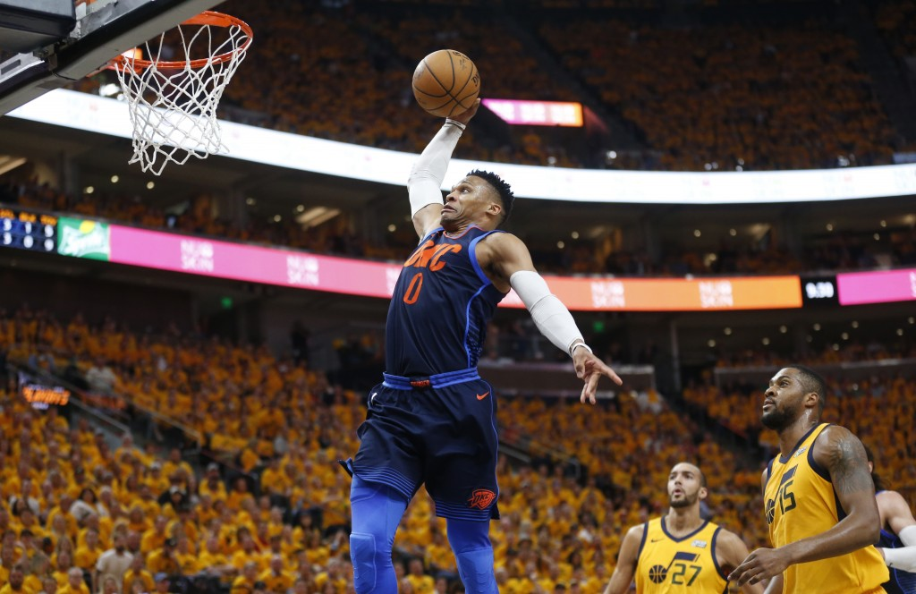 Oklahoma City Thunder guard Russell Westbrook goes up for a dunk as Utah Jazz's Rudy Gobert (27) and Derrick Favors (15) watch during the first half o...