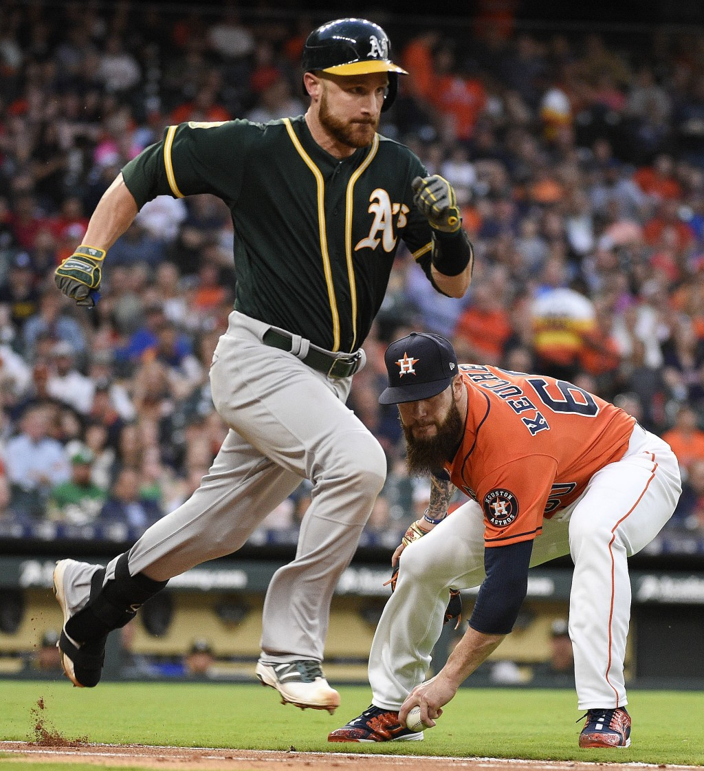 Houston Astros starting pitcher Dallas Keuchel, right, fields the ground ball of Oakland Athletics' Jonathan Lucroy, left, during the third inning of ...