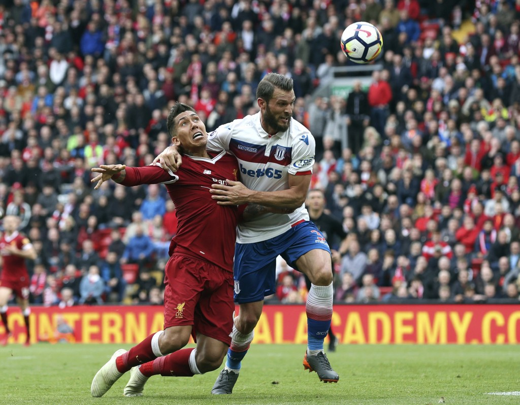 Liverpool's Roberto Firmino, left and Stoke City's Erik Pieters battle for the ball, during the English Premier League soccer match between Liverpool ...