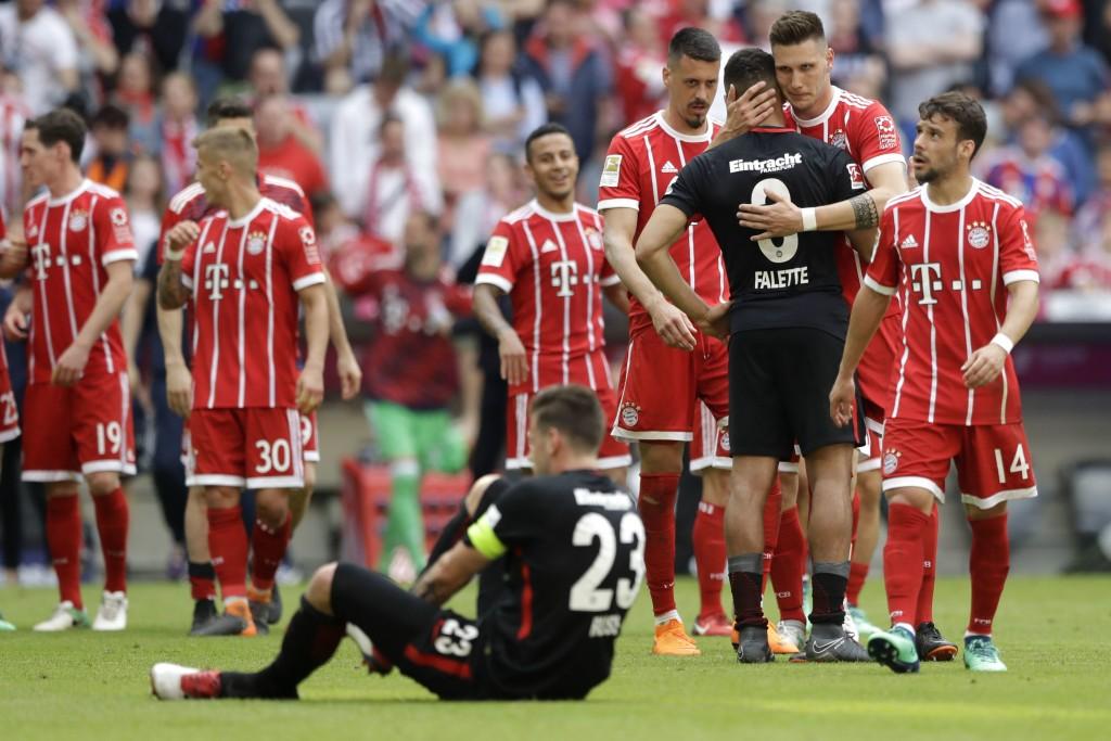 Bayern's Niklas Suele hugs Frankfurt's Simon Falette after the German Bundesliga soccer match between FC Bayern Munich and Eintracht Frankfurt at the ...