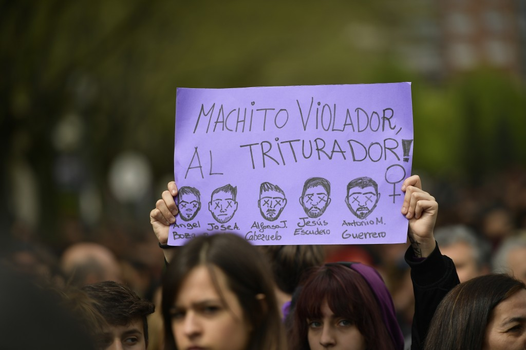 A demonstrator holds up a sign painted with the faces of a group known ''La Manada'' or Pack Leader, reading, ''Male Violator to the Crusher'' during ...