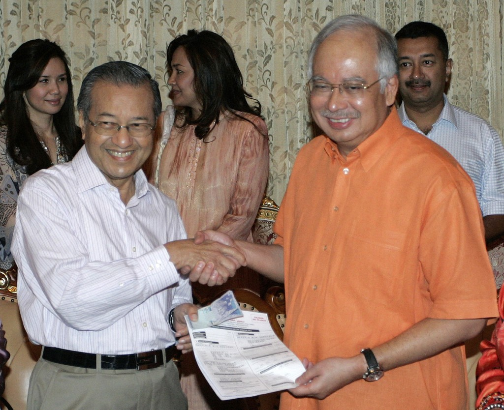 FILE - In this April 4, 2009, file photo, Malaysian Prime Minister Najib Razak, right, receives the party form from former Prime Minister Mahathir Moh...