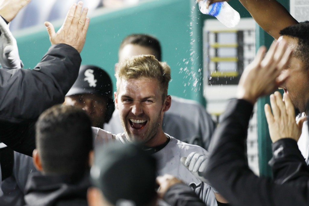 Chicago White Sox designated hitter Matt Davidson is congratulated in the dugout after hitting a two-run home run in the 11th inning of a baseball gam...
