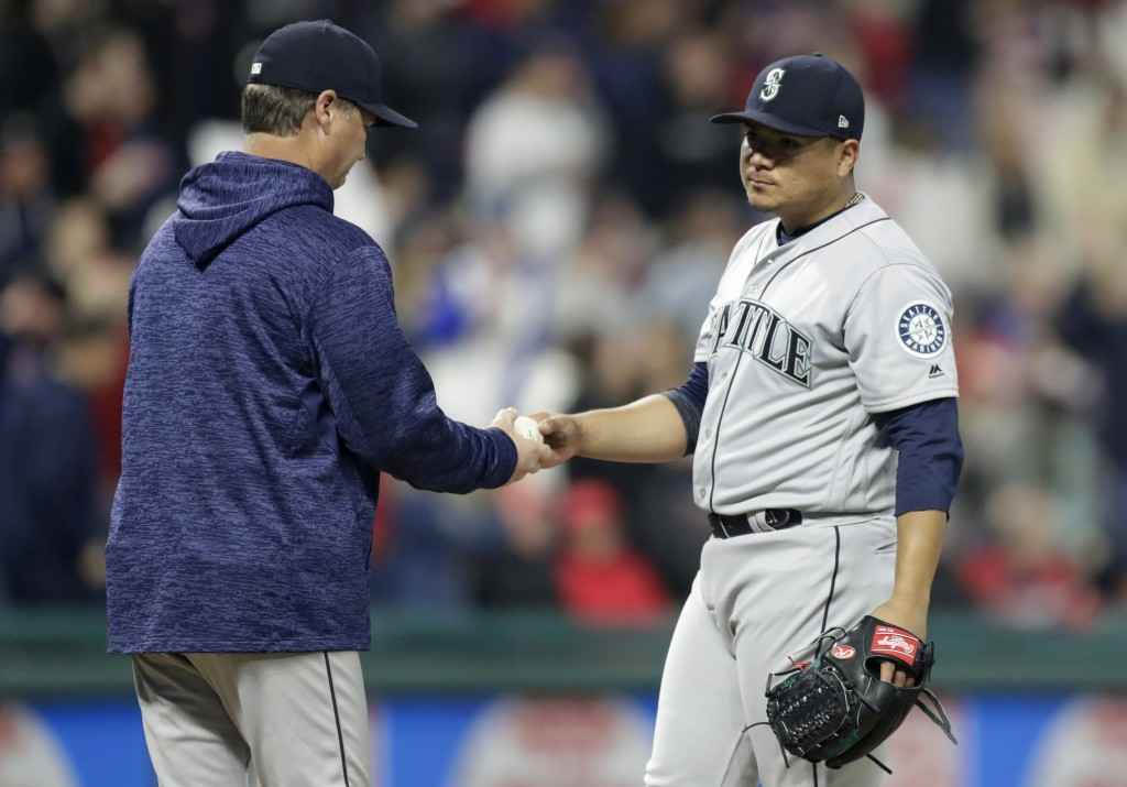 Seattle Mariners starting pitcher Erasmo Ramirez, right, hands the ball to manager Scott Servais during the sixth inning of the team's baseball game a...