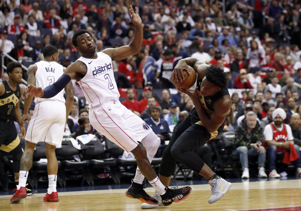 Washington Wizards guard John Wall (2) fouls Toronto Raptors forward OG Anunoby, right, during the first half of Game 6 of an NBA basketball first-rou...