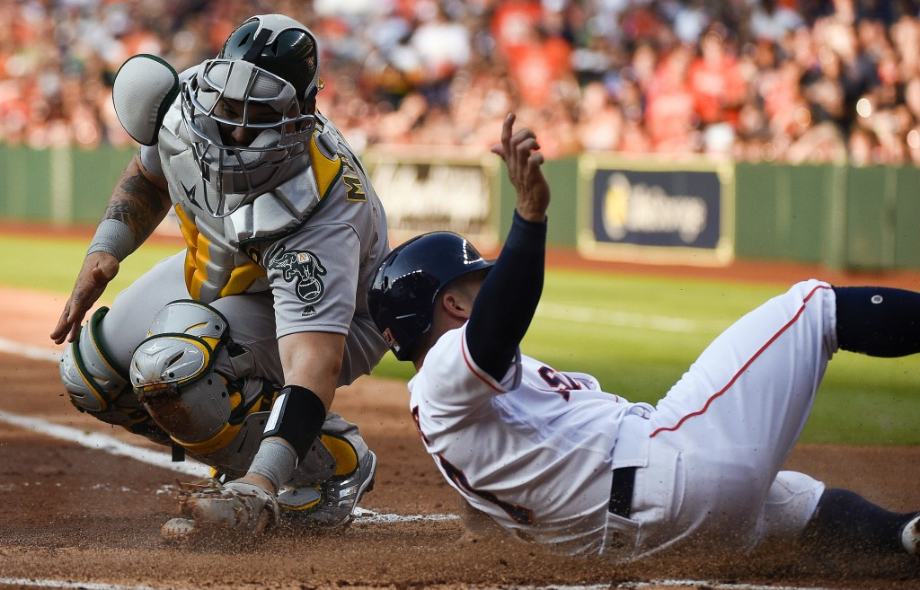 Houston Astros' Jose Altuve, right, slides safely past Oakland Athletics catcher Bruce Maxwell to score on Josh Reddick's sacrifice fly during the fir...