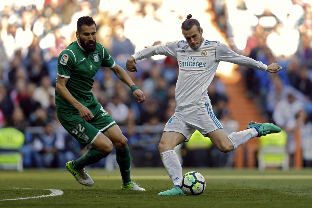 Real Madrid's Gareth Bale, right, shoots the ball next to Leganes' Dimitrios Siovas during a Spanish La Liga soccer match between Real Madrid and Lega...