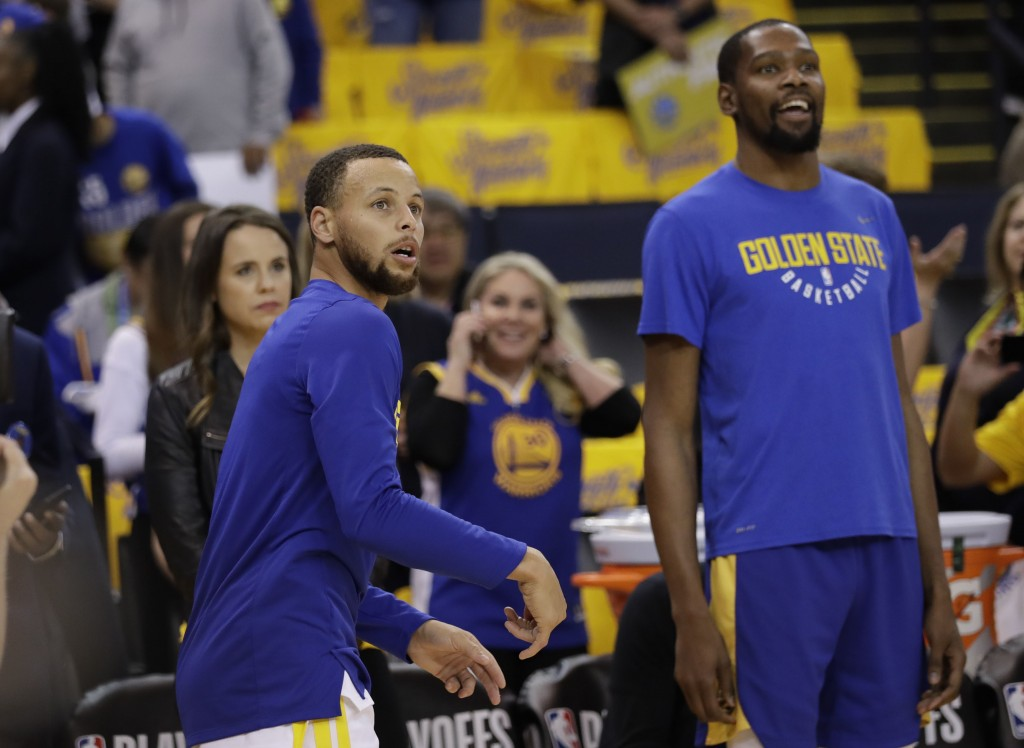 Golden State Warriors' Stephen Curry, left, watches his shot next to teammate Kevin Durant as players warm up for Game 1 of an NBA basketball second-r...