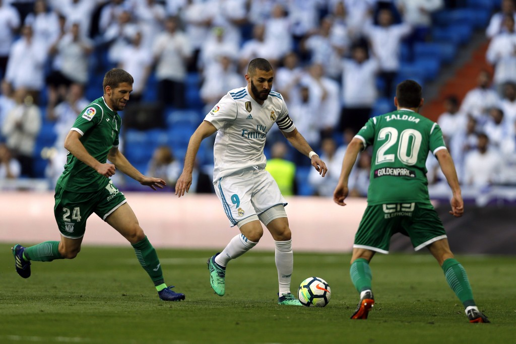 Real Madrid's Karim Benzema, centre, vies for the ball with Leganes' Darko Brasanac, left, and Joseba Zaldua during a Spanish La Liga soccer match bet...