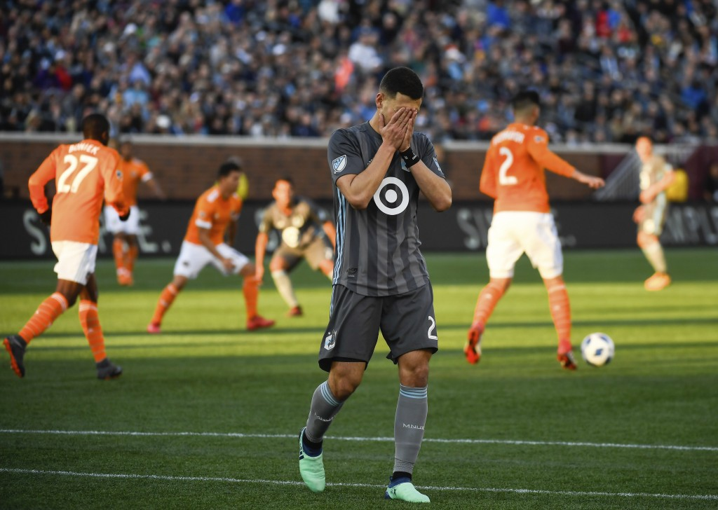 Minnesota United forward Christian Ramirez reacts after suffering an apparent injury, during the first half of an MLS soccer match against the Houston...