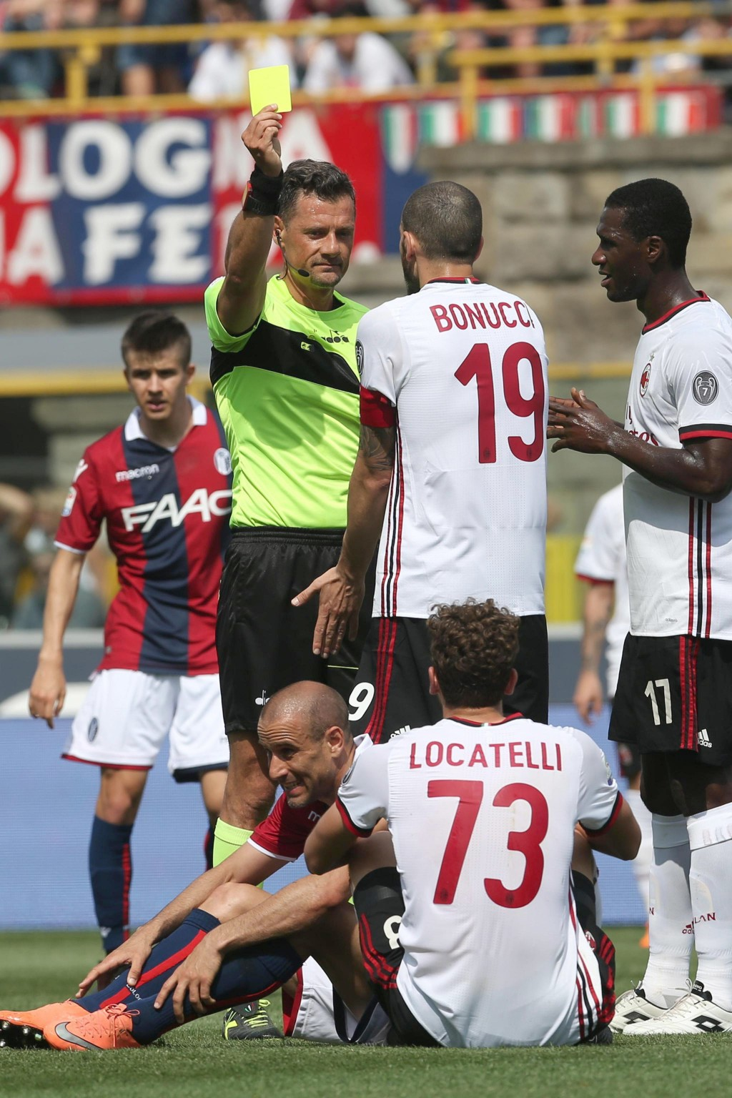 Referee Piero Giacomelli shows a yellow card to AC Milan's Manuel Locatelli, on the ground, as AC Milan's Leonardo Bonucci argues with him during a se...