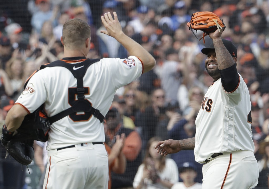 San Francisco Giants' Pablo Sandoval, right, high-fives catcher Nick Hundley (5) after pitching against the Los Angeles Dodgers during the ninth innin...