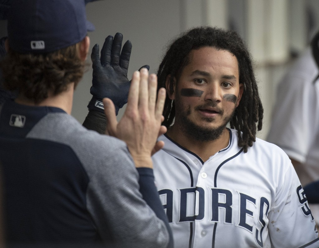 San Diego Padres' Freddy Galvis is welcomed in the dugout after scoring during the third inning of a baseball game against the New York Mets in San Di...