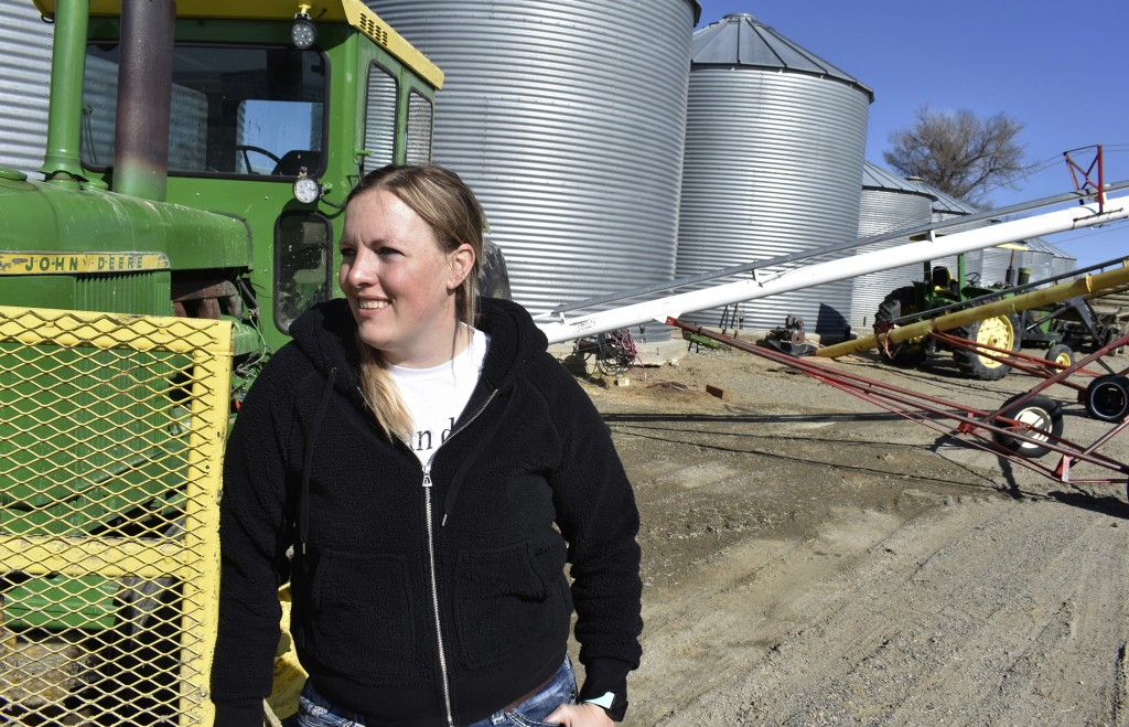 In this April 20, 2018, photo, Michelle Erickson Jones poses for a photograph in front of a tractor and grain silos at Erickson Farm in Broadview, Mon...
