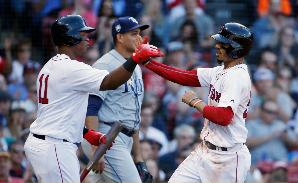 Boston Red Sox's Mookie Betts, right, celebrates with teammate Rafael Devers (11) after scoring on a sacrifice fly by Xander Bogaerts during the first...