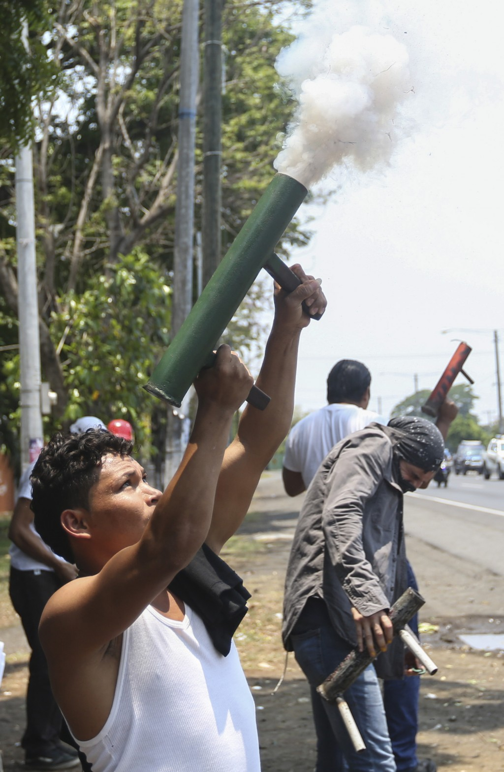 """University students of the """"Universidad Nacional Agraria,"""" fire homemade mortars into the air as they show their support to the caravan of peasants ar..."""