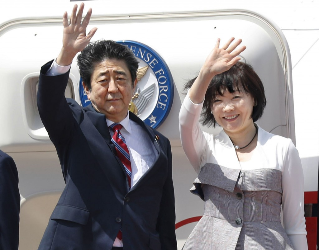 Japanese Prime Minister Shinzo Abe, left,  waves with his wife Akie Abe while boarding his plane before departure for the Middle Eastern countries, at...