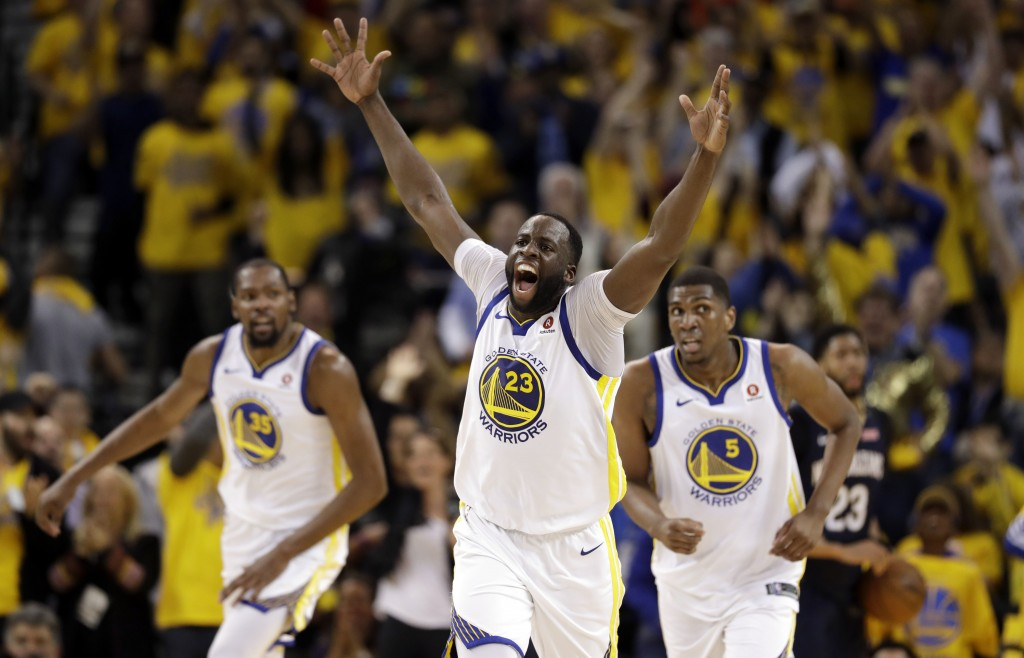 Golden State Warriors' Draymond Green (23) reacts after feeding an alley-oop pass for a dunk by Kevin Durant, left, during the first half in Game 1 of...