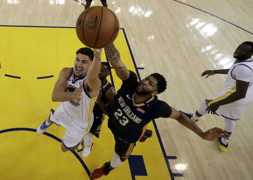 Golden State Warriors' Klay Thompson, left, shoots while New Orleans Pelicans' Anthony Davis (23) defends during the second half in Game 1 of an NBA b...