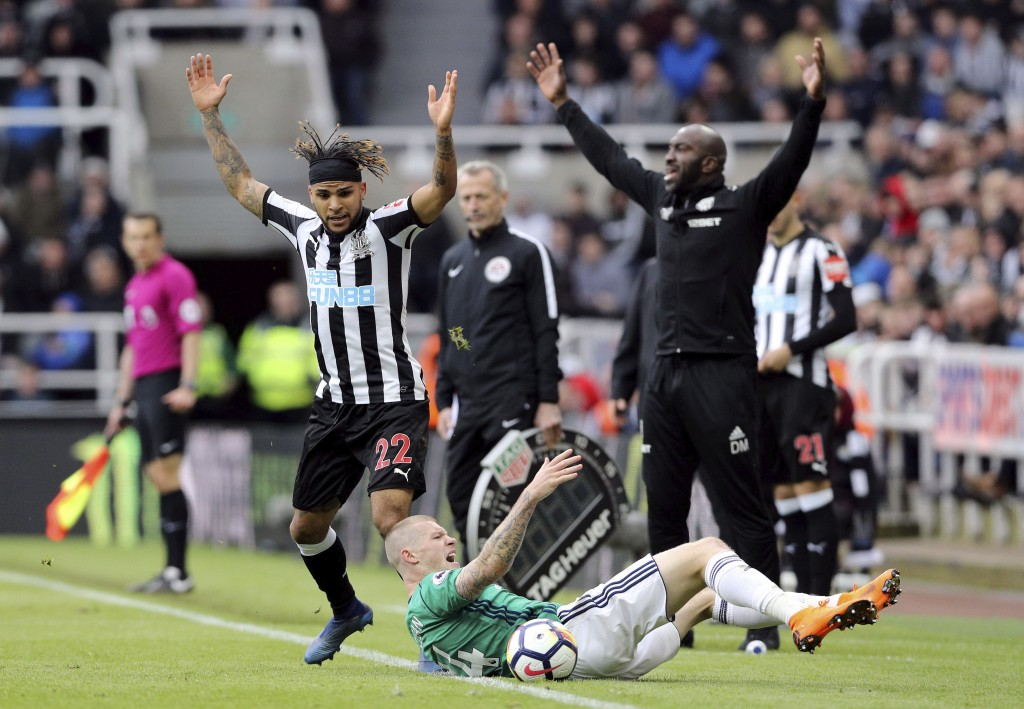 West Bromwich Albion's James McClean, bottom, goes down as Newcastle United's DeAndre Yedlin, left, and West Bromwich Albion caretaker manager Darren ...