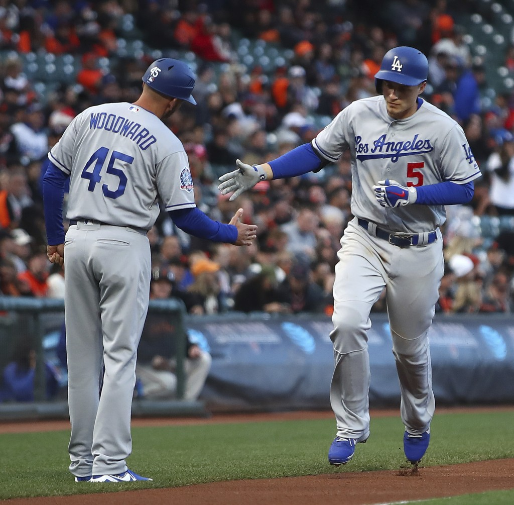 Los Angeles Dodgers' Corey Seager, right, is congratulated by third base coach Chris Woodward (45) after hitting a two-run home run off San Francisco ...