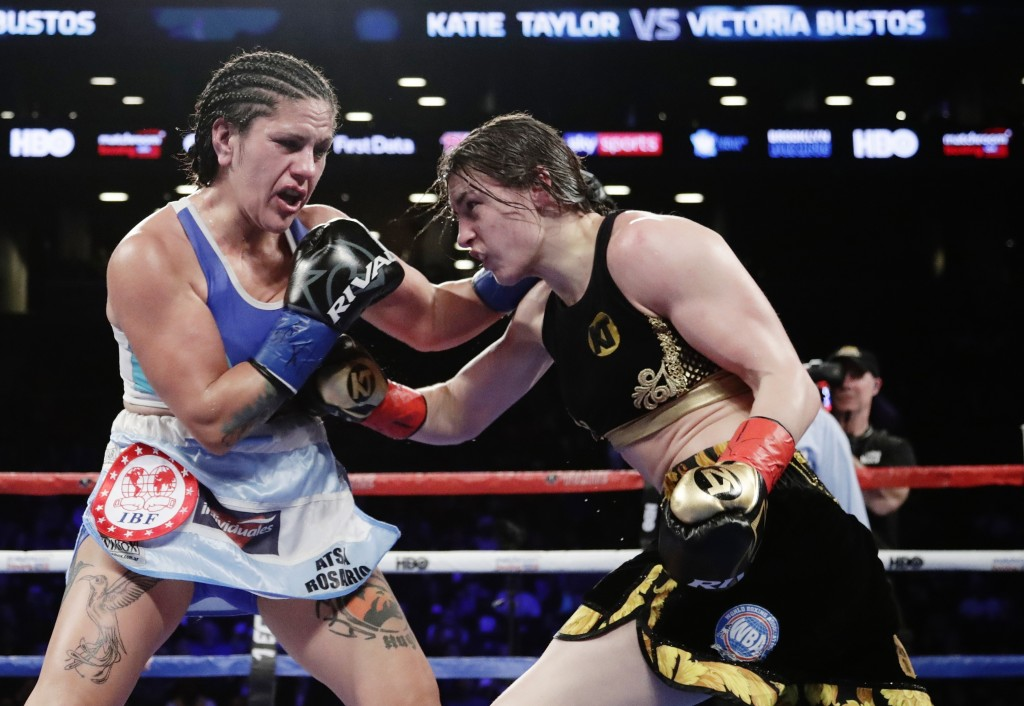 Ireland's Katie Taylor, and Argentina's Victoria Noelia Bustos trade blows during the ninth round of a women's lightweight championship boxing match S...