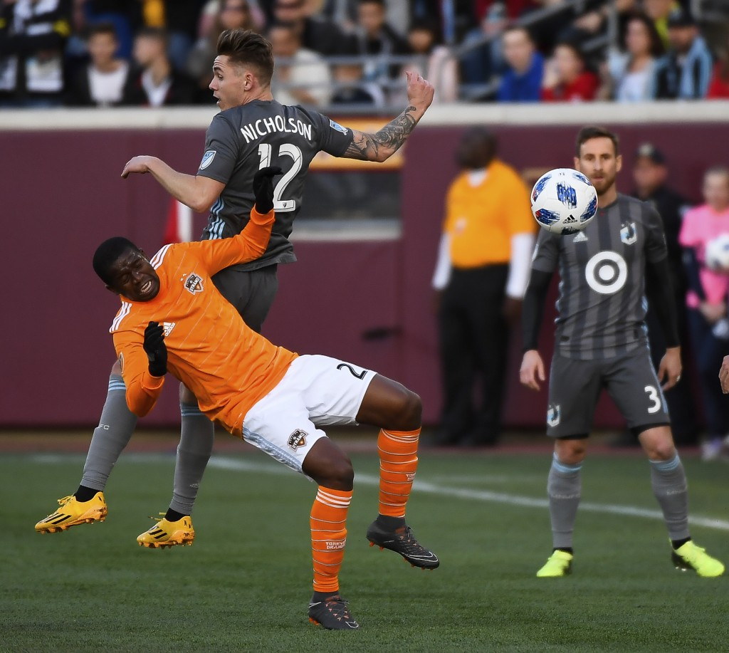 Houston Dynamo midfielder Oscar Garcia (27) and Minnesota United midfielder Sam Nicholson (12) collide while jumping for a header during the first hal...