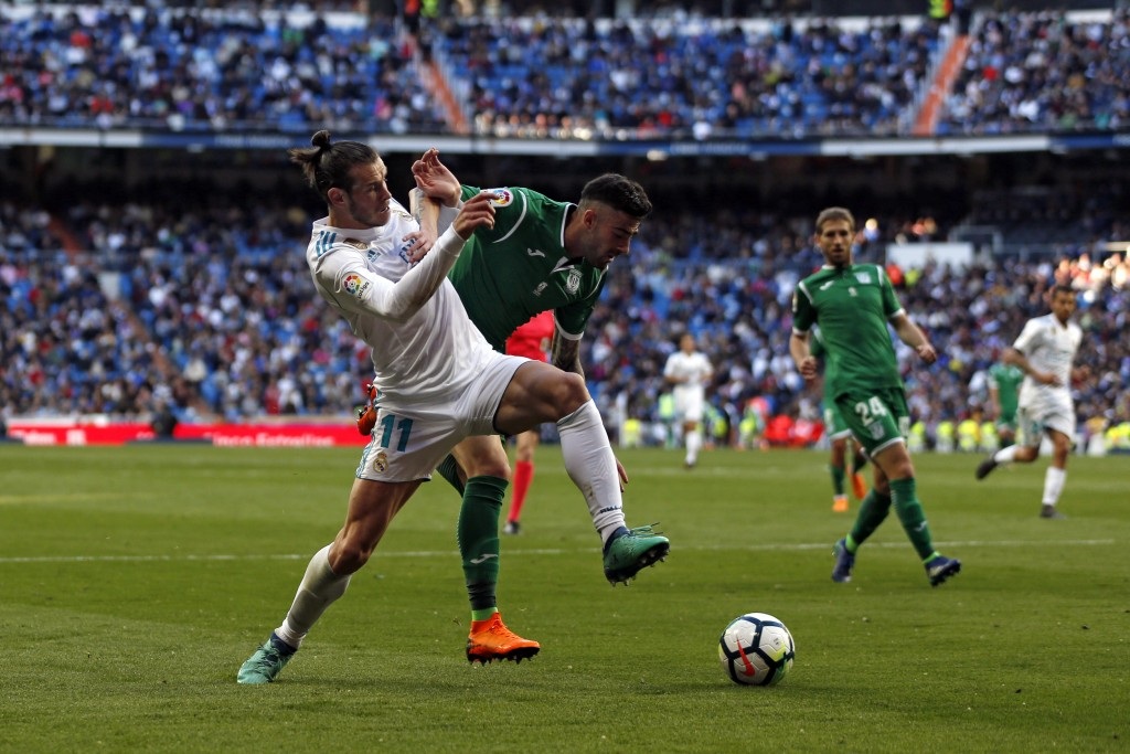 Real Madrid's Gareth Bale, left, tussles for the ball with Leganes' Diego Rico during a Spanish La Liga soccer match between Real Madrid and Leganes a...