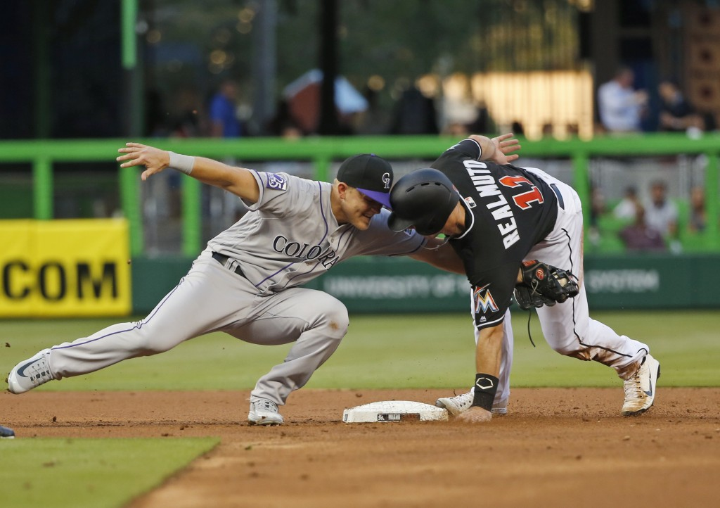 Colorado Rockies second baseman Pat Valaika, left, attempts to tag Miami Marlins' J.T. Realmuto (11) after Realmuto stole second during the first inni...