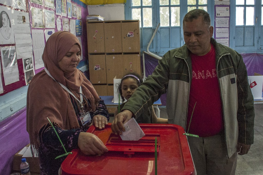 A Tunisian policeman dressed in civilian clothing, right, accompanied by his daughter casts his vote during municipal elections at a polling station f...