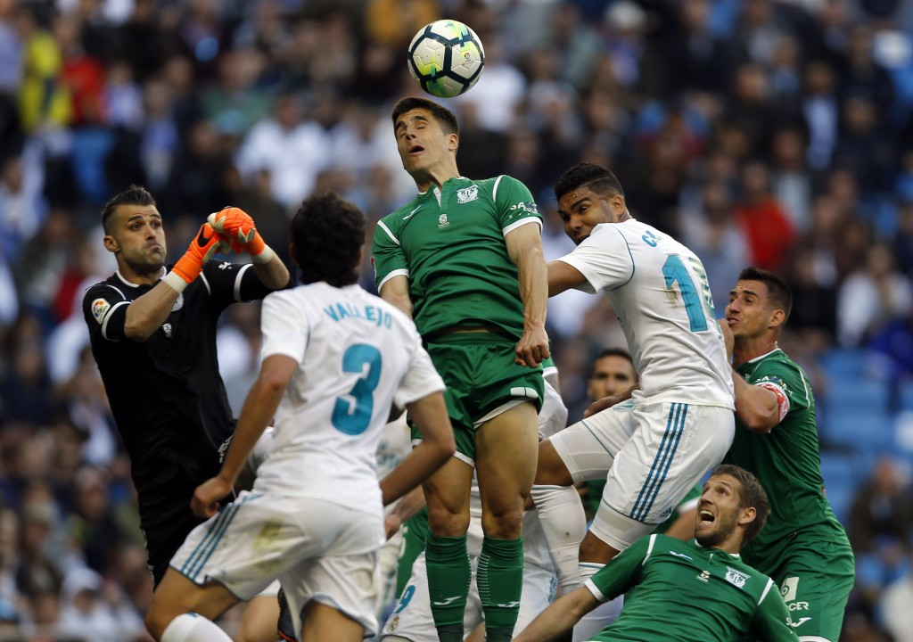 Leganes' Unai Bustinza, top, out jumps Real Madrid players during a Spanish La Liga soccer match between Real Madrid and Leganes at the Santiago Berna...