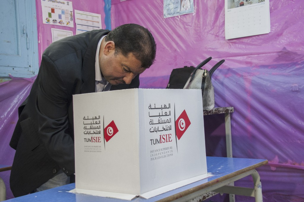 A Tunisian policeman dressed in civilian clothing casts his vote during municipal elections at a polling station for the police and military in Tunis,...