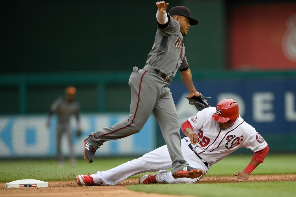Washington Nationals' Pedro Severino (29) is tagged out by Arizona Diamondbacks second baseman Ketel Marte, front, during the third inning of a baseba...