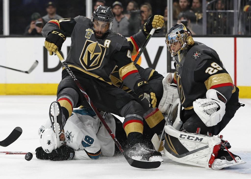 Vegas Golden Knights left wing Pierre-Edouard Bellemare (41) falls over San Jose Sharks center Tomas Hertl (48) while beside Golden Knights goaltender...