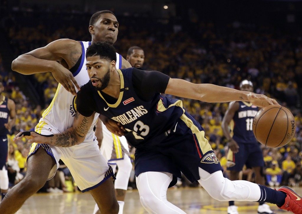 New Orleans Pelicans' Anthony Davis, right, is defended by Golden State Warriors' Kevon Looney during the first half in Game 1 of an NBA basketball se...