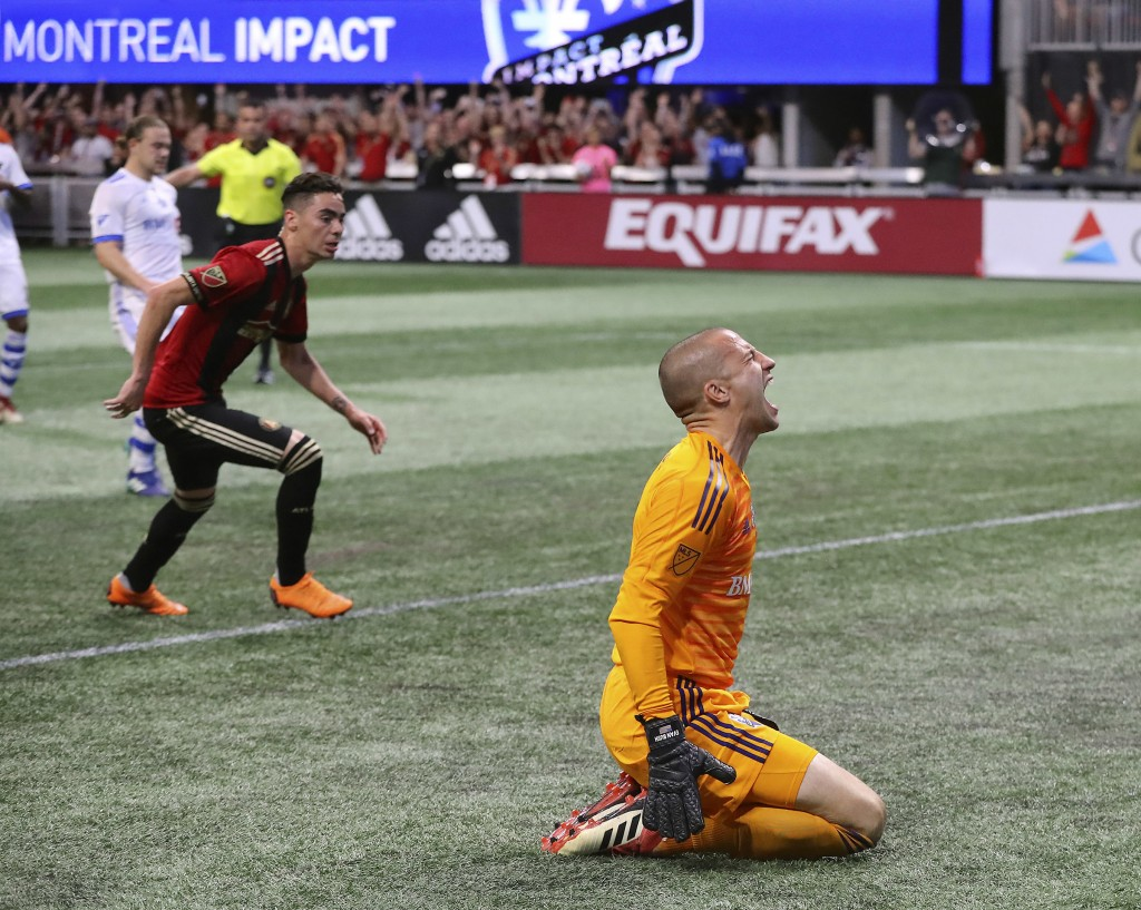 Montreal Impact goalkeeper Evan Bush reacts as Atlanta United midfielder Miguel Almiron, left, scores on a penalty kick during the second half of an M...