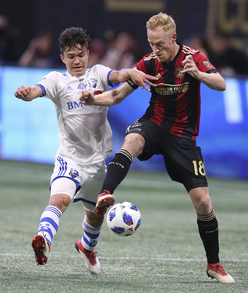 Atlanta United midfielder Jeff Larentowicz and Montreal Impact midfielder Ken Krolicki battle for the ball during the first half in a MLS soccer game ...