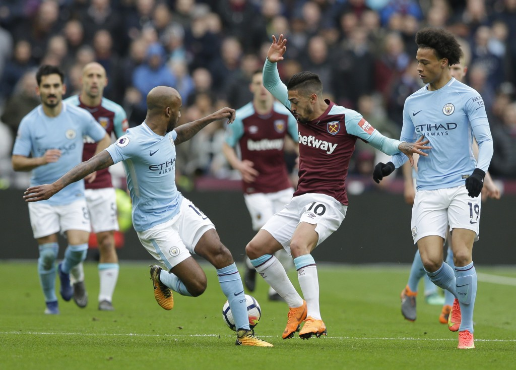 West Ham United's Manuel Lanzini , centre, attempts to control the ball from Manchester City's Fabian Delph, left, during the English Premier League s...