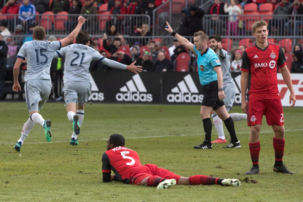 Toronto FC defender Ashtone Morgan, center, and Liam Fraser, right, react after Chicago Fire's Alan Gordon, center left, scored during second-half MLS...
