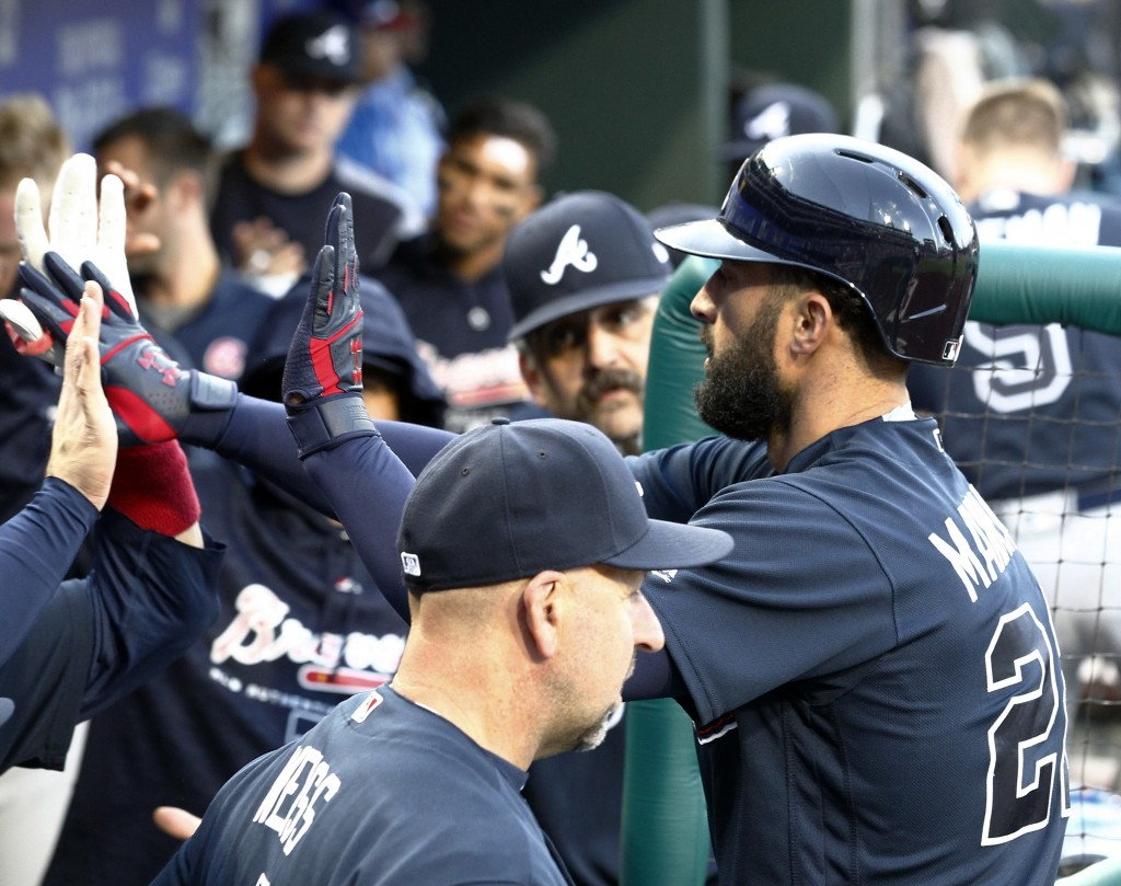 Atlanta Braves' Nick Markakis high-fives teammates in the dugout after hitting a solo home run during the second inning of a baseball game against the...