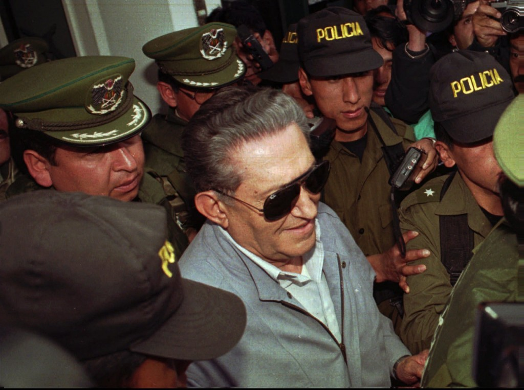 FILE  - In this  Jan 17 1997 file photo, Bolivia's jailed, ex-dictator Luis Garcia Meza is surrounded by police as he leaves the Copacabana clinic in ...