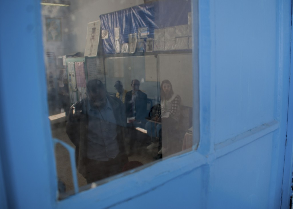 A Tunisian policeman dressed in civilian clothing, left, casts his vote during municipal elections at a polling station for the police and military in...