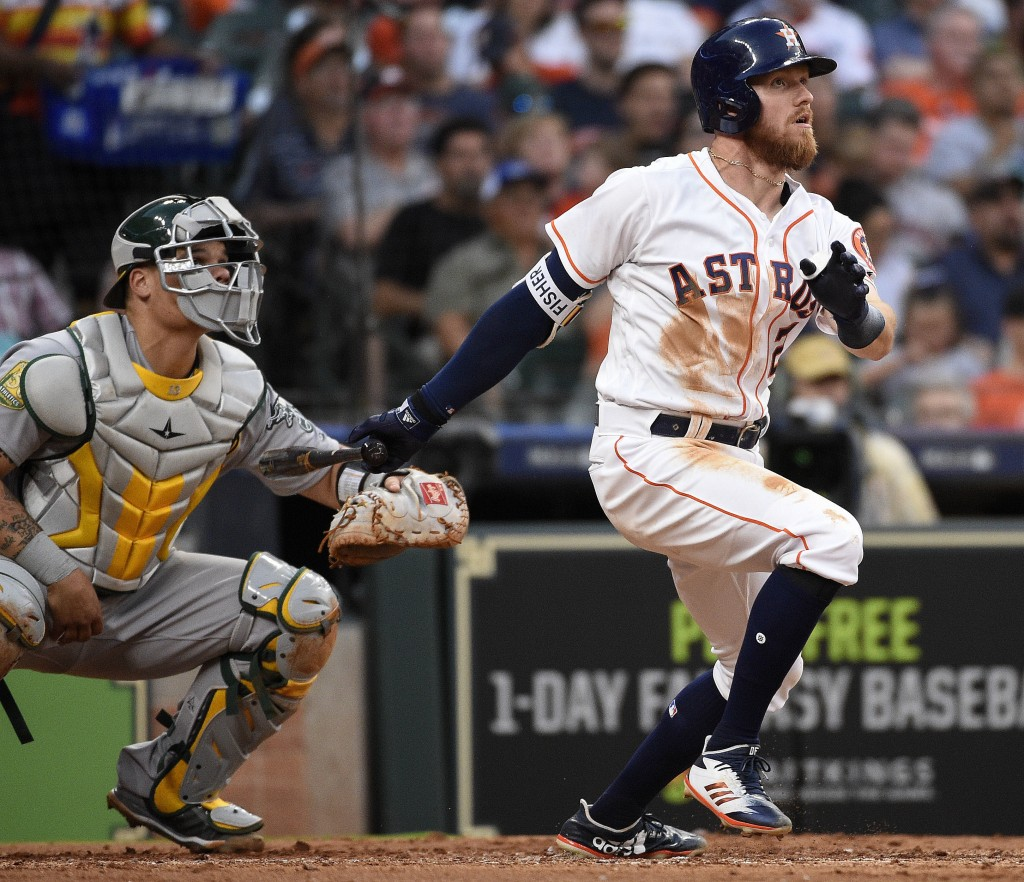 Houston Astros' Derek Fisher, right, watches his two-run home run off Oakland Athletics relief pitcher Daniel Coulombe during the fourth inning of a b...