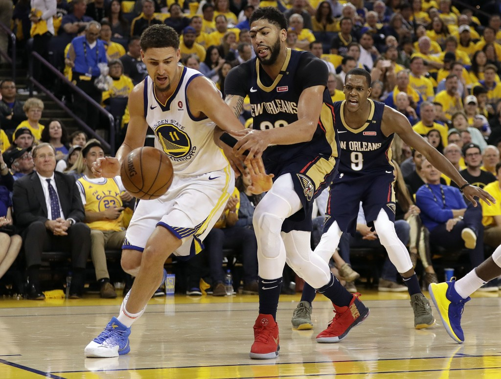 Golden State Warriors' Klay Thompson, left, is defended by New Orleans Pelicans' Anthony Davis, center, during the second half in Game 1 of an NBA bas...