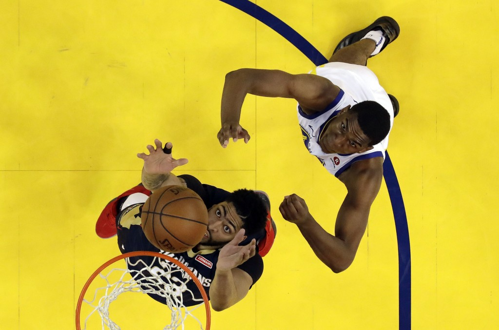 New Orleans Pelicans' Anthony Davis, bottom grabs a rebound next to Golden State Warriors' Kevon Looney during the second half in Game 1 of an NBA bas...