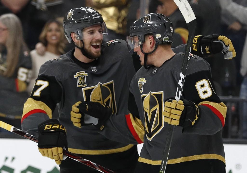 Vegas Golden Knights defenseman Shea Theodore, left, celebrates after defenseman Nate Schmidt, right, scored a goal against the San Jose Sharks during...
