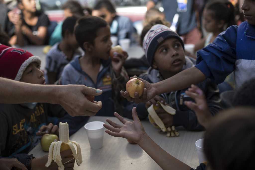 "Children have their breakfast at the ""Vina de Tijuana AC"" migrant shelter in Tijuana, Mexico, Saturday, April 28, 2018. As the migrants prepare to wal..."