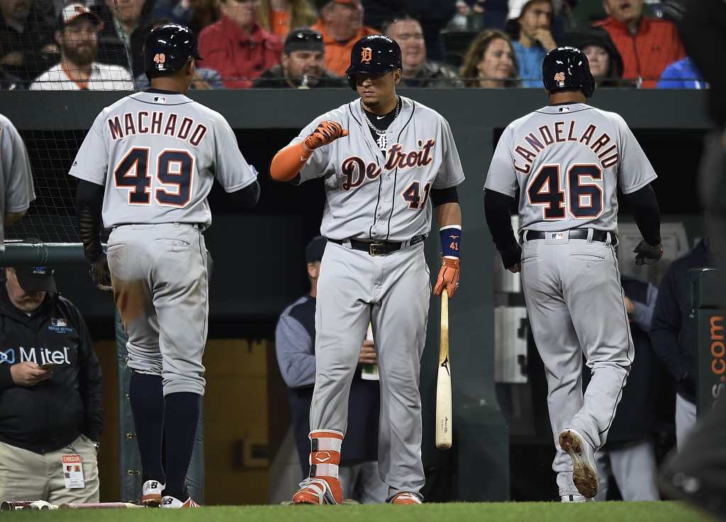 Detroit Tigers Victor Martinez, center congratulates Dixon Machado, left, and Jeimer Candelario after they scored against the Baltimore Orioles in the...