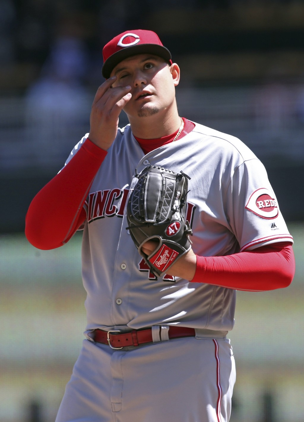 Cincinnati Reds' pitcher Sal Romano wipes his face after giving up a walk to Minnesota Twins' Ehire Adrianza in the third inning of a baseball game Sa...